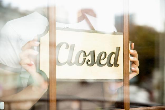 Zamknięty znak na szkle z odbiciem ulicznej kawiarni lub restauracji. pandemia koronawirusa nowe zasady bezpieczeństwa. zamknięcie w czasie kwarantanny, kryzys. ścieśniać.