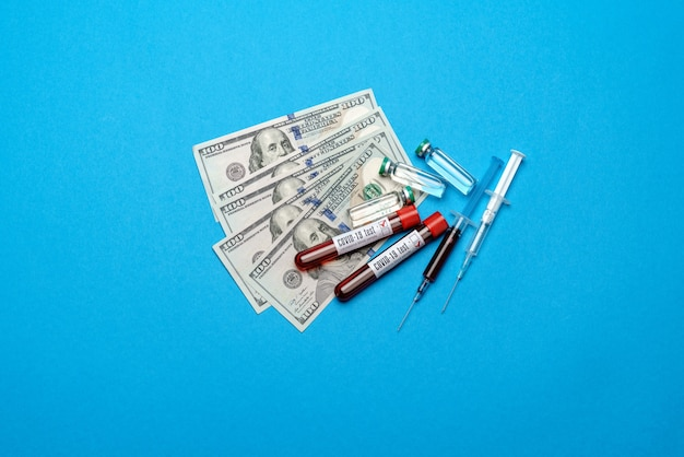 Zamknij 100 dolarowych rachunków, ampułki szczepionek i próbki krwi w probówce