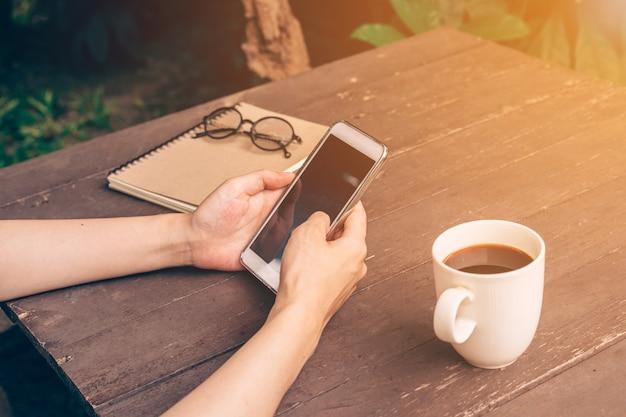Zamknij a? asian kobieta za pomoc? telefonu w kawiarni i sunlight z rocznika filtr.