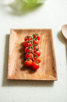 Zamknij a? zdj? cie drewnianej tablicy prostok? tnej i oddzia? u pomidorów cherry na jej temat