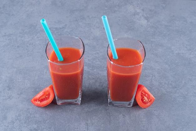 Zamknij a? zdj? cie dwóch szklanek soku pomidorowego i plasterków pomidora.