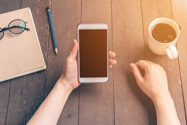 Zamknij azjatyckich dłoni kobieta przy użyciu telefonu w kawiarni z rocznika filtr.
