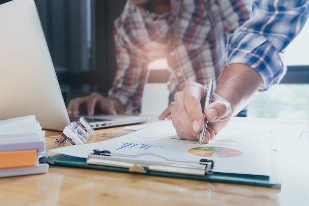 Zamknij biznes ludzi r? ce na pracy z planu finansowego i na drewniane biurko w biurze. koncepcja wsparcia grupowego.