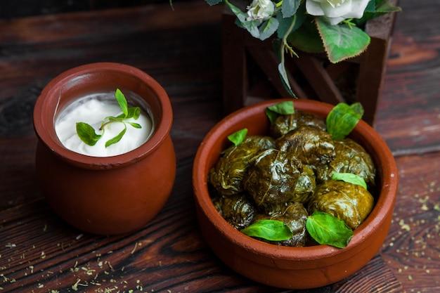 Zamknij ciemne liście winogron nadziewane mięsem i ryżem z sosem śmietanowym na ciemnym drewnianym stole. tradycyjna kuchnia wschodnioeuropejska i azjatycka