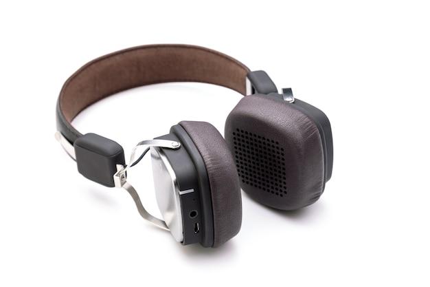 Zamknij czarne słuchawki lub zestaw słuchawkowy na białej powierzchni. skopiuj miejsce na tekst lub projekt