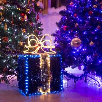 Zamknij.duże pudełko z prezentami świątecznymi w pobliżu choinki w salonie