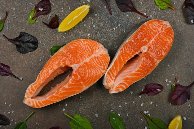 Zamknij dwa świeże surowe steki z łososia na stole, z kawałkami cytryny i liśćmi sałaty, podwyższony widok z góry, bezpośrednio nad