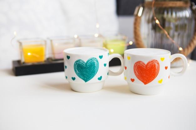 Zamknij dwie filiżanki cappuccino, świece i wazon z eukaliptusem