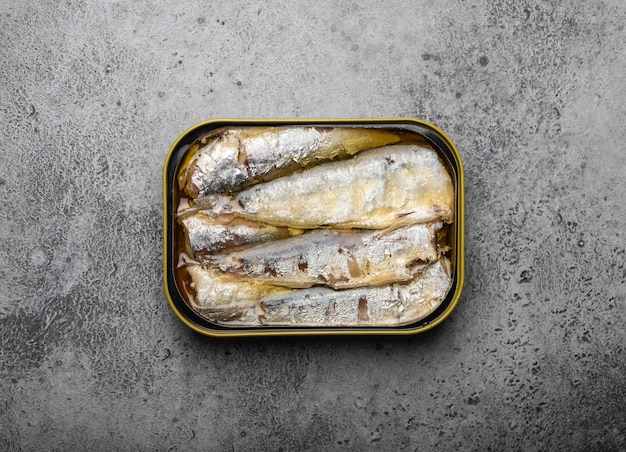 Zamknij i widok z góry sardynki w puszkach w puszce na szarym tle rustykalnym betonu. ryby w puszce jako wygodny, szybki i zdrowy pokarm oraz źródło kwasów tłuszczowych omega-3, białka i witaminy d