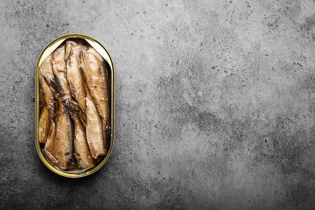 Zamknij i widok z góry wędzonej sardynki w puszkach w puszce na szarym tle, miejsca na tekst. ryby w puszce jako wygodny, szybki i zdrowy pokarm oraz źródło kwasów tłuszczowych omega-3, białka i witaminy d