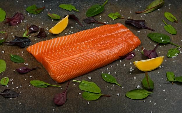 Zamknij jeden świeży surowy filet z łososia na stole, z ćwiartkami cytryny i liśćmi sałaty, wysoki kąt widzenia