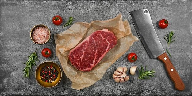 Zamknij jeden wiekowy stek wołowy z surowej polędwicy wołowej na brązowym papierze pergaminowym, z tasakiem i przyprawami na tle kamiennego stołu, podwyższony widok z góry, bezpośrednio nad