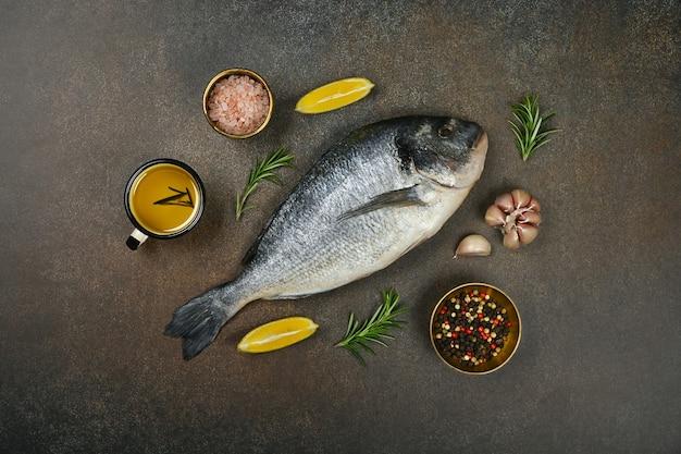 Zamknij jedną świeżą surową dorada dorada na stole, z solą, ziarnami pieprzu, rozmarynem, czosnkiem i oliwą z oliwek, podwyższony widok z góry, bezpośrednio nad