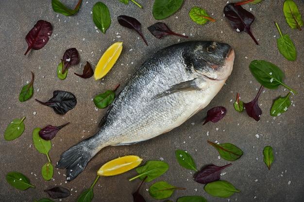 Zamknij jedną świeżą surową rybę dorady na stole, z klinami cytryny i liśćmi sałaty, podwyższony widok z góry, bezpośrednio nad