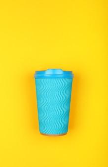 Zamknij jedną zaciśniętą jednorazową, pastelową niebieską papierową filiżankę kawy na wynos na żywym żółtym tle, płasko ułożona, podwyższony widok z góry, bezpośrednio nad