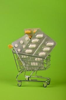 Zamknij kilka różnych opakowań blistrowych tabletek w małym koszyku na zielonym tle, koncepcja dostawy zamówienia leków online, niski kąt widzenia