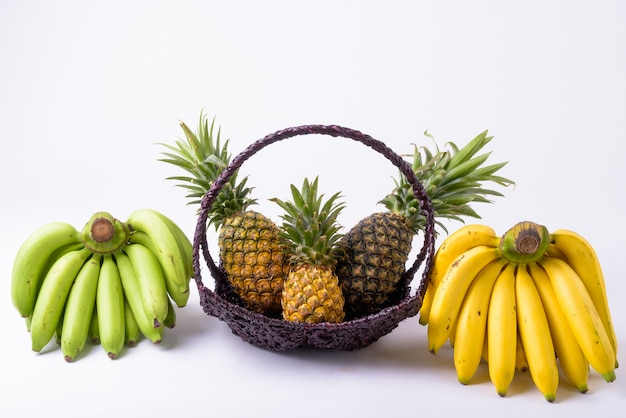 Zamknij kosz z ananasami i bananami z boku