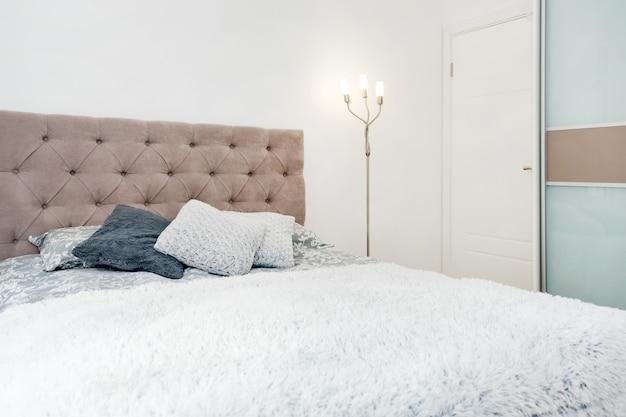 Zamknij łóżko z kolorowymi poduszkami, narzutą i przytulną lampą.