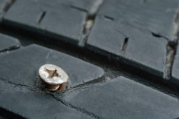 Zamknij metalowe śruby, gwoździe wyhaftowane w oponach