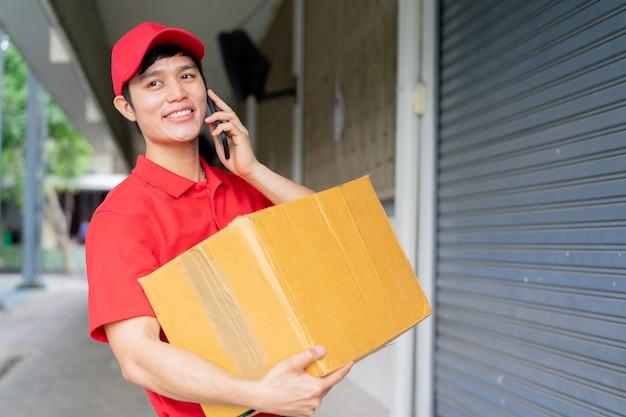 Zamknij młodego pracownika pocztowego (w czerwonym mundurze), niosąc pudełko i stań przed domem, używając smartfona wzywając klienta do zamówienia