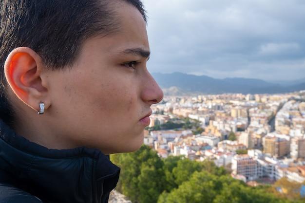 Zamknij młody chłopak patrząc z boku na miasto malaga w hiszpanii.
