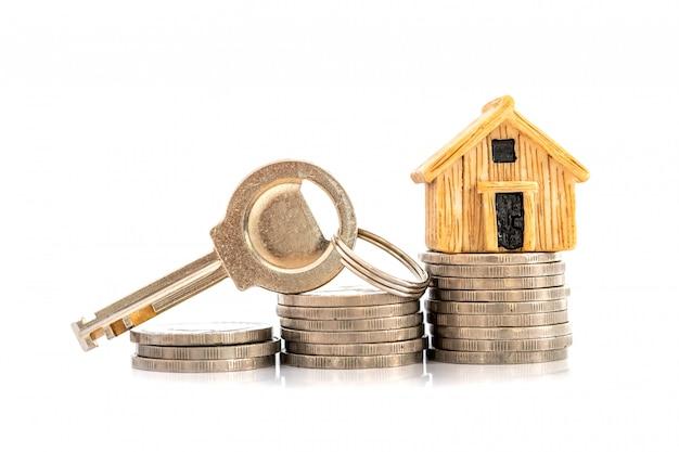 Zamknij model domu, miejsce na stosie monet pieniędzy na hipotekę i pożyczkę, refinansowanie lub inwestycję w nieruchomości