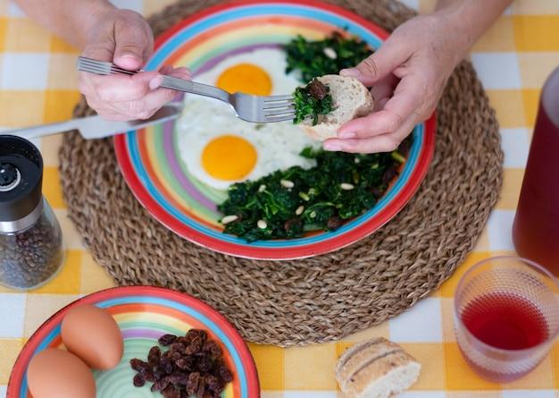 Zamknij naczynie z jajkami i szpinakiem z orzeszkami pinii i rodzynkami. kieliszek na żółtym obrusie