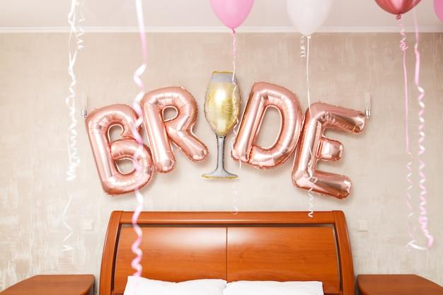 """Zamknij napis """"panna młoda"""" z różowych balonów w pokoju hotelowym. dzień ślubu. szczegóły ślubu się spuchły. poranek narzeczonych"""