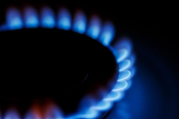 Zamknij niebieski płomień palnika gazowego kuchenki kuchennej w ciemności