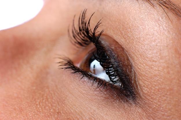 Zamknij niebieskie oko z naturalnym makijażem patrząc z boku