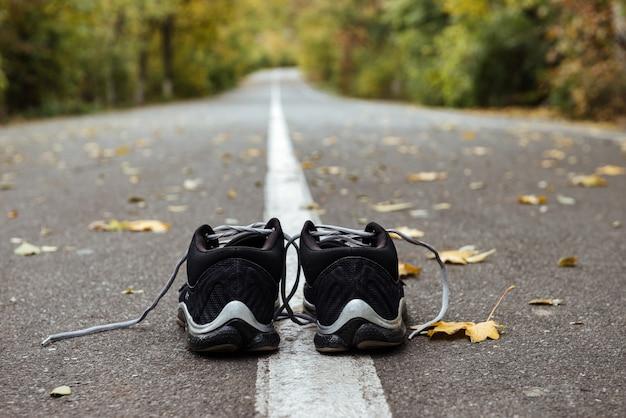 Zamknij nowe czarne buty do biegania na asfaltowej drodze na oznaczeniach drogowych