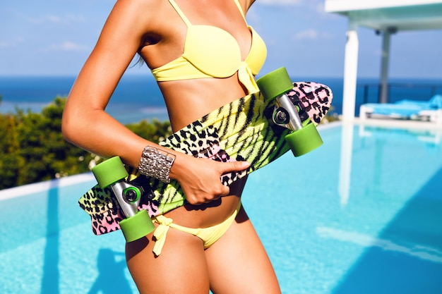 Zamknij obraz mody pięknej kobiety z idealnym ciałem i tyłkiem trzymającej deskorolkę, pozującej w pobliżu luksusowego basenu z niesamowitym widokiem na tropikalną wyspę, ubrana w seksowne neonowe żółte bikini.