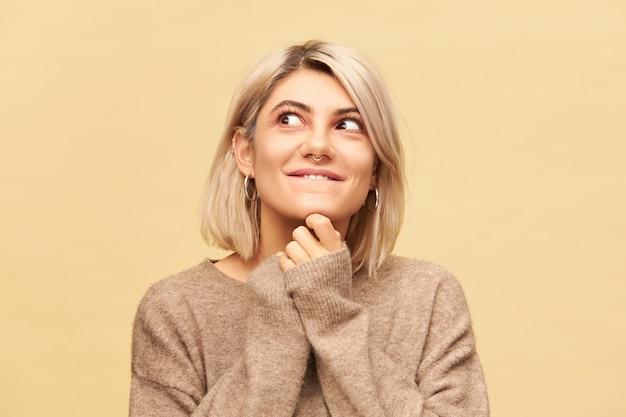 Zamknij obraz uroczej młodej blondynki noszącej kolczyk w nosie i strzyżonej fryzurze, trzymającej się za ręce pod brodą i odwracającej wzrok z figlarnym, tajemniczym uśmiechem, robiąc figle i psot