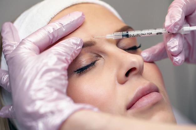 Zamknij ostrożną kosmetyczkę, która wstrzykuje botox w okolice brwi. koncepcja zabiegów kosmetycznych