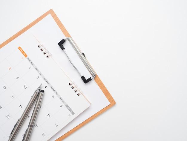 Zamknij pióro w kalendarzu z tablicą na dokumenty na widoku z góry na białym tle na kopię