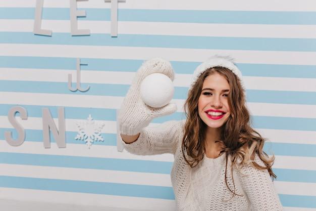 Zamknij portret kobiety słowiańskie z przyjaznym uśmiechem, zabawę z śnieżną kulą ziemską