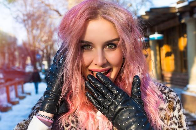 Zamknij portret ładnej kobiety z różowymi, niezwykłymi falującymi włosami, pozującej zimą na zaśnieżonej ulicy, z pięknymi oczami, uśmiechem i stylowymi skórzanymi rękawiczkami z ćwiekami w rockowym stylu.