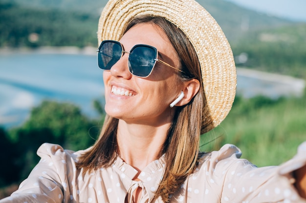 Zamknij portret młodej kobiety z okulary i kolczyki w ciepłym zachodzie słońca w parku