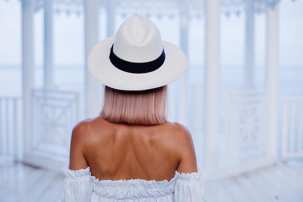 Zamknij portret moda na zewnątrz stylowej kobiety w obszernym białym modnym topie i klasycznym luksusowym kapeluszu i lampartowych okularach przeciwsłonecznych
