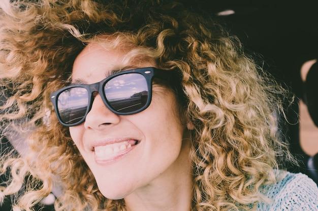 Zamknij portret pięknej młodej dorosłej kobiety kaukaski wesoły szczęśliwy uśmiech i patrzeć na drogę odzwierciedloną na okulary przeciwsłoneczne podczas podróży samochodem