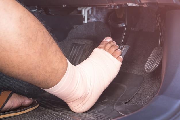 Zamknij prawą stopę z tkaniny bandaż krok na hamulce w nowoczesnym samochodzie.
