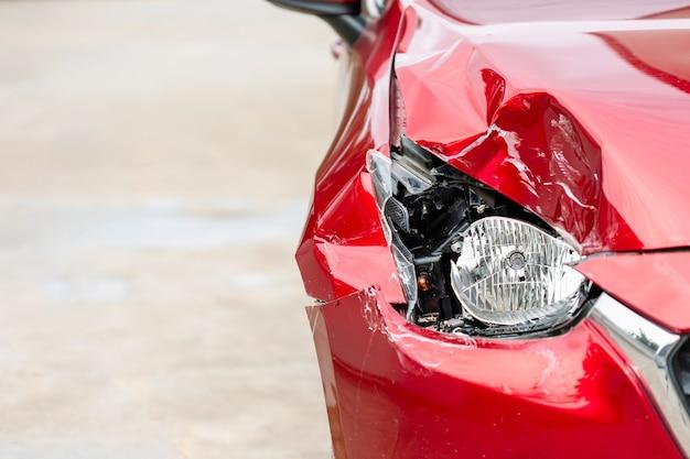 Zamknij prawy przód czerwonego, nowoczesnego samochodu, który został uszkodzony przez przypadek. skopiuj miejsce na tekst lub reklamę koncepcji ubezpieczenia lub naprawy samochodu