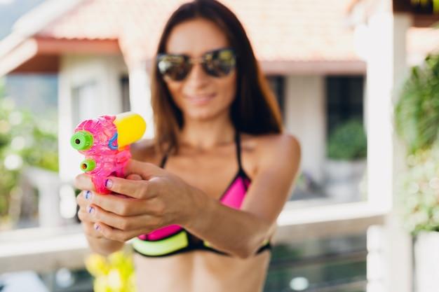 Zamknij ręce całkiem uśmiechniętej szczęśliwej kobiety bawiącej się zabawką watergun w basenie na letnich tropikalnych wakacjach w hotelu willowym, bawiąc się w kostiumie kąpielowym bikini, kolorowy styl, imprezowy nastrój
