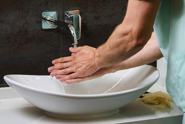 Zamknij ręce lekarza pod bieżącą wodą w celu ochrony przed pandemią koronowirusa