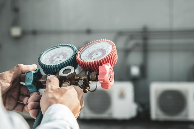 Zamknij rękę inżyniera używającego miernika kolektora pomiarowego do napełniania klimatyzatora przemysłowego.