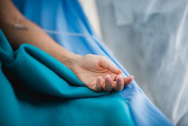 Zamknij rękę pacjenta, w sali w sali operacyjnej szpitala z lekarzem i personelem gabinetu medycznego