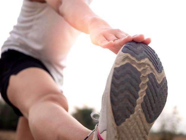 Zamknij rękę rozciągającą nogę i stopy przed treningiem