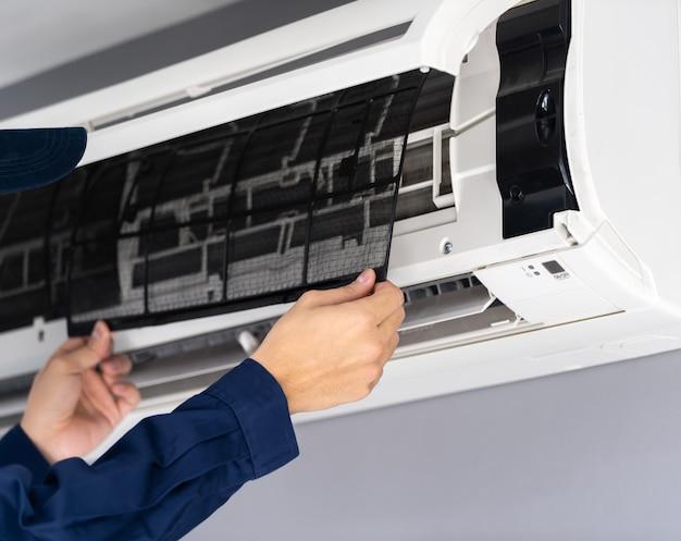 Zamknij serwisant usuwający filtr powietrza z klimatyzatora do czyszczenia