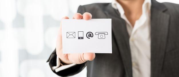 Zamknij si? biznesmen przedstawiaj? cy bia ?? kart? z ikonami kontaktu koncepcyjne centrum informacji biznesowych i wsparcie
