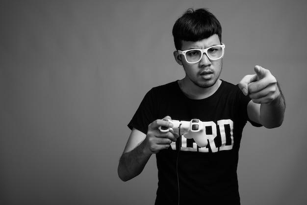 Zamknij si? m? odych azjatyckich nerd cz? owieka noszenie okularów podczas grania w gry